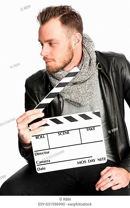 Attractive young man in his 20s sitting down wearing a black leather jacket holding a film slate. White background