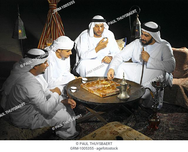 Arab men playing backgammon in Arabian tent