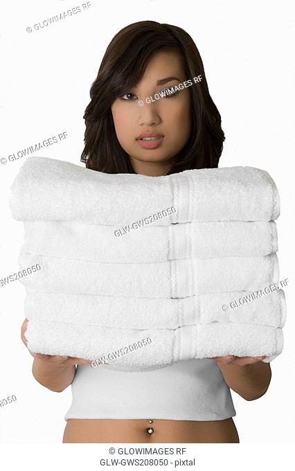 Portrait of a young woman holding a stack of folded towels