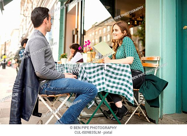 Couple at pavement cafe looking at menu smiling