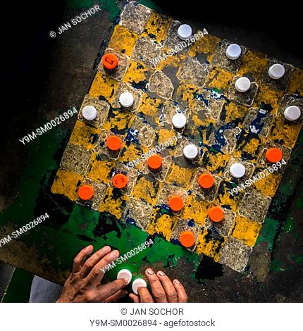 Hands of a Salvadoran man are seen holding plastic bottle caps while playing checkers on an outdoor checkerboard table in the park in San Salvador, El Salvador