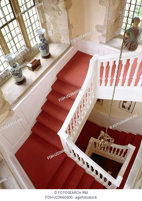 Aerial view of red carpet on white Georgian staircase with stone mullion windows