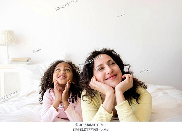 Mother and daughter daydreaming on bed