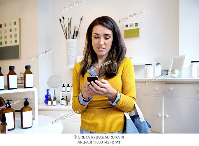 Woman with smartphone in perfume store