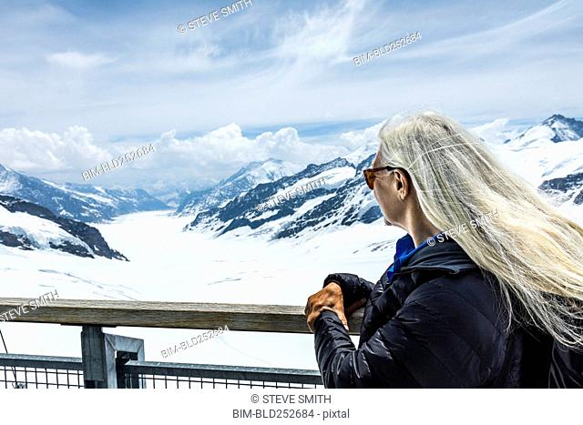 Caucasian woman leaning on railing admiring scenic view of mountains