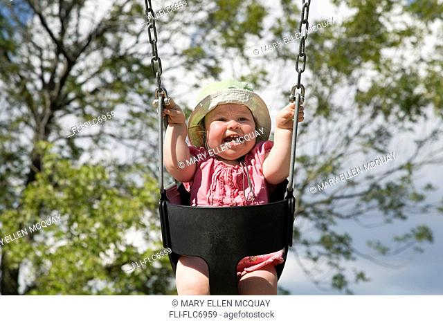 Baby girl laughing while she swings, Ontario, Canada