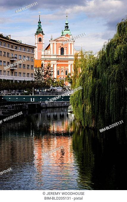 Ornate church on urban river, Ljubljana, Slovenia