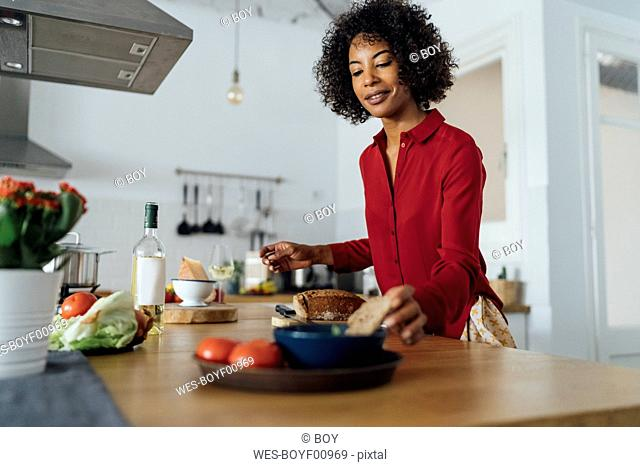 Woman standing in kitchen, slicing bread