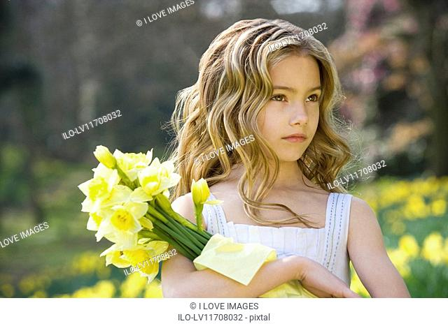 A portrait of a young girl holding a bunch of daffodils