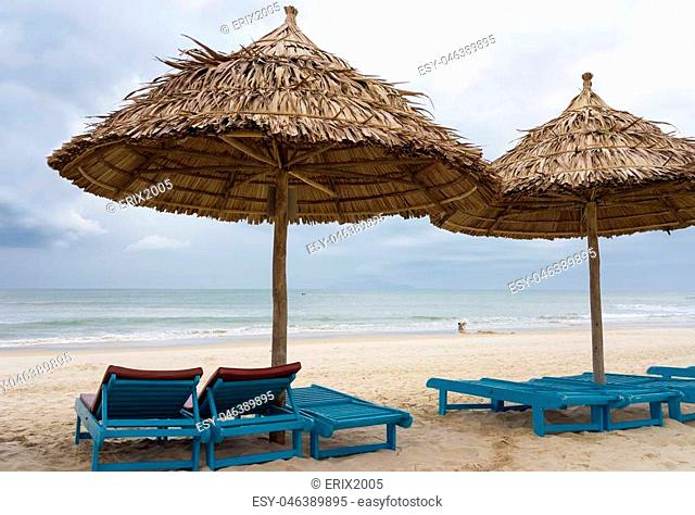 Sunbeds and Palm shelters in the China Beach in Da Nang, Vietnam. It is also called Non Nuoc Beach. South China Sea on the background