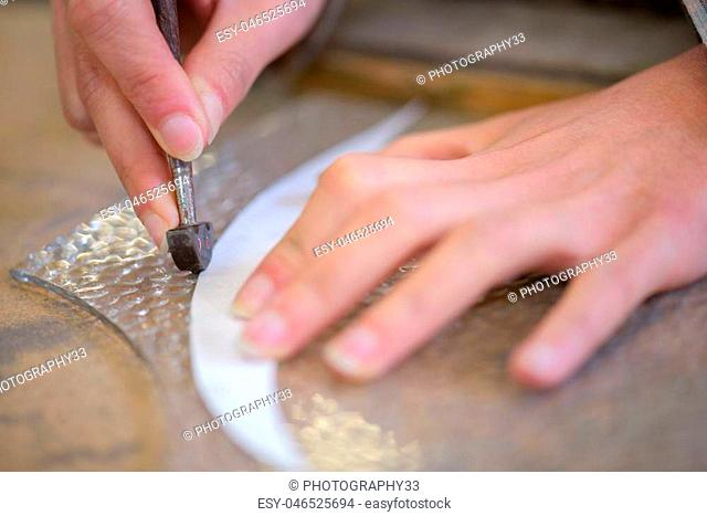 Hands cutting glass from template