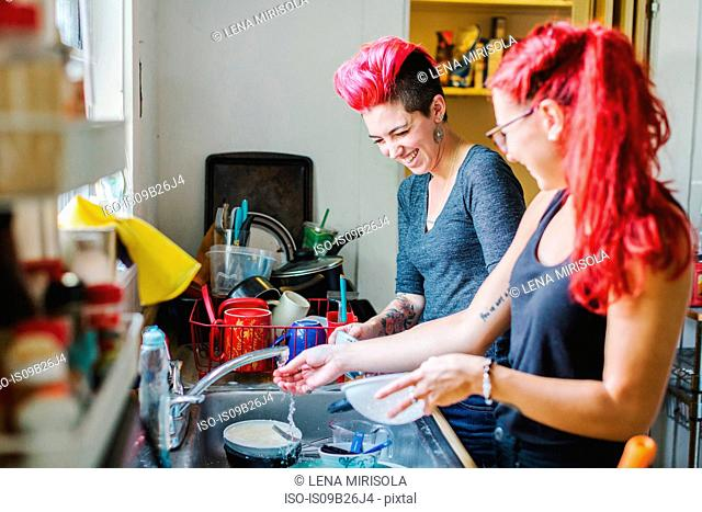 Two young women with pink hair laughing whilst washing dishes at kitchen sink