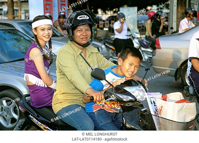 Phitsanulok. Crowded street in town. Traffic. Cars. A woman in a helmet riding a motorbike. With a woman riding pillion behind him and a child sitting on the...