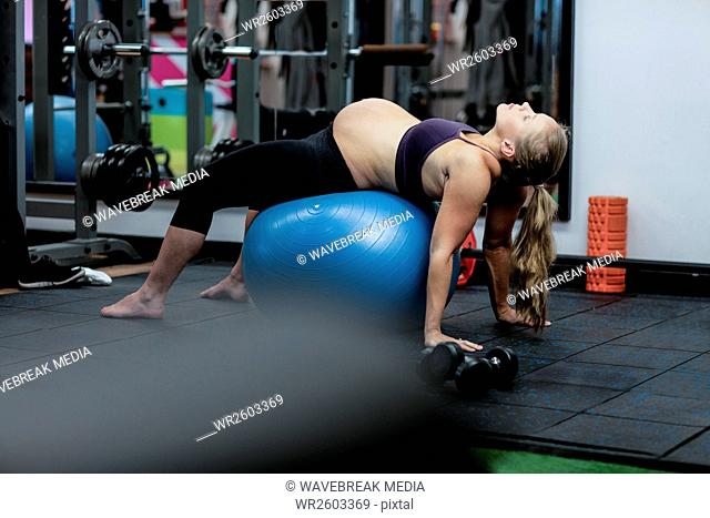 Pregnant woman performing stretching exercise on fitness ball