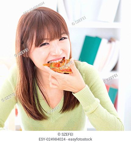 Asian girl eating pizza at home. Female living lifestyle indoors