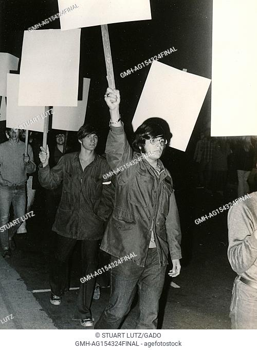 A group of students wearing hippie attire march at night carrying signs during an anti Vietnam War student sit-in protest at North Carolina State University