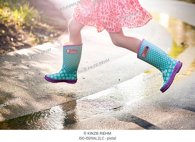 Waist down view of girl jumping puddles on rainy street