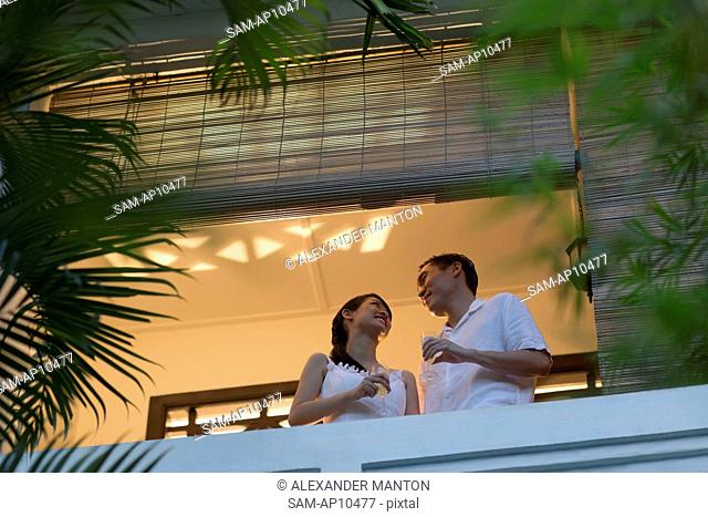 Singapore, Mid-adult couple with champagne talking on balcony