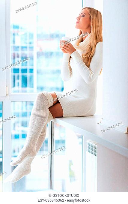 Enjoying good day at home. Beautiful young blond hair woman in warm sweater and socks enjoying coffee and keeping eyes closed while sitting in front of the...