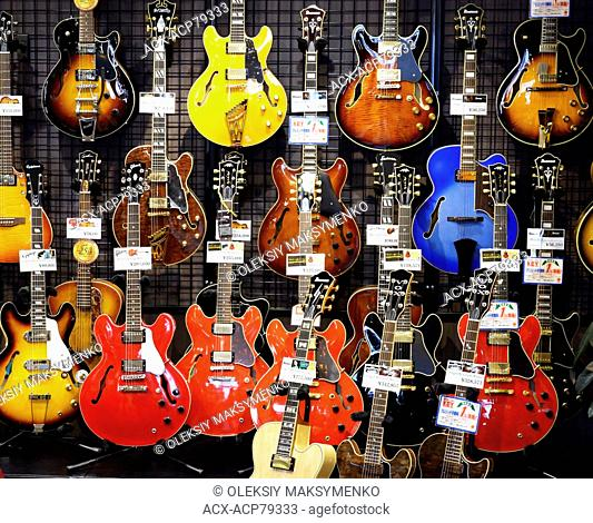 Semi-acoustic hollow-body electric guitars on display in a music store in Tokyo, Japan