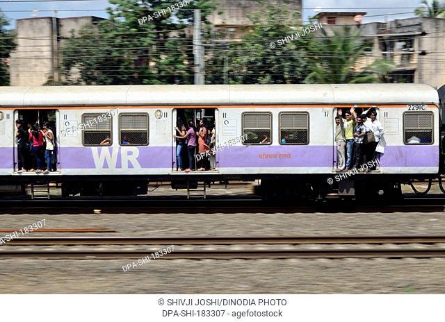 people travelling in Local train at Mumbai Maharashtra India