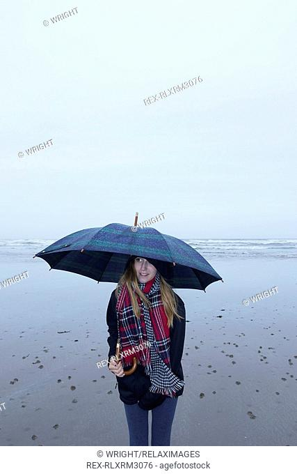 Teenage girl looking away while holding umbrella on beach during rainy season