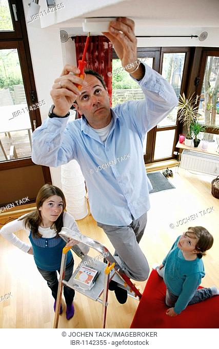 Man installing a smoke detector in the apartment, his daughters watching him, Germany, Europe