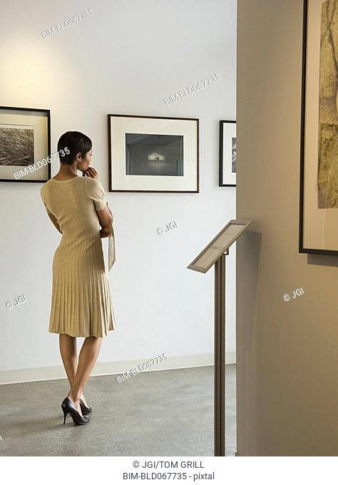 African woman enjoying photographs in museum