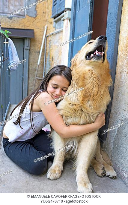 Little girl with her dog golden retriever