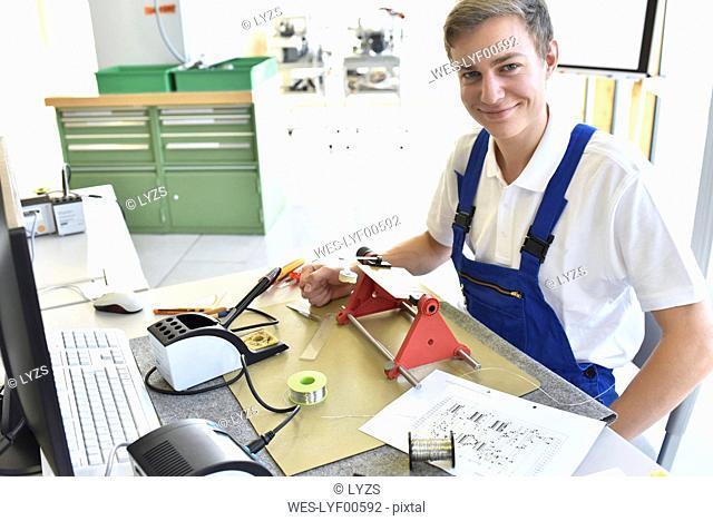Smiling student assembling circuit board