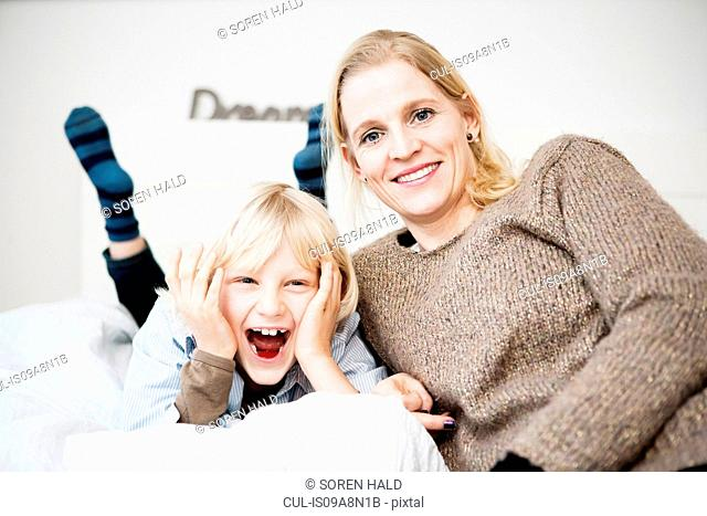 Fun portrait of mother and son on bed