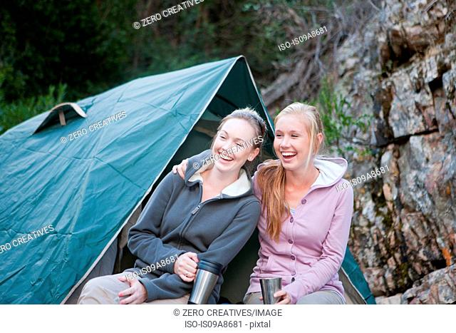 Two young girls sitting in front of tent