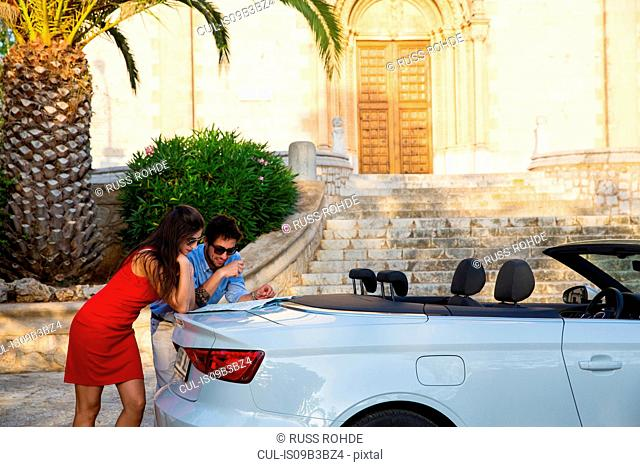 Young couple leaning against convertible looking at map, Calvia, Majorca, Spain