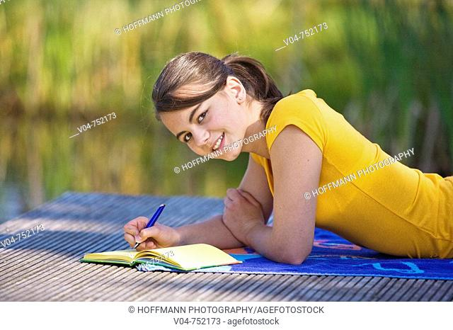 Teenaged girl lying on a footbridge and writing in her diary, smiling at the camera