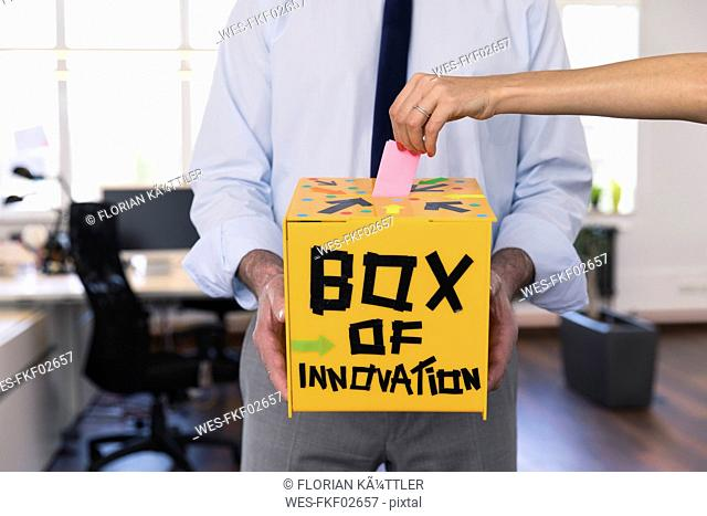 Businessman collecting innovative suggestions in yellow box