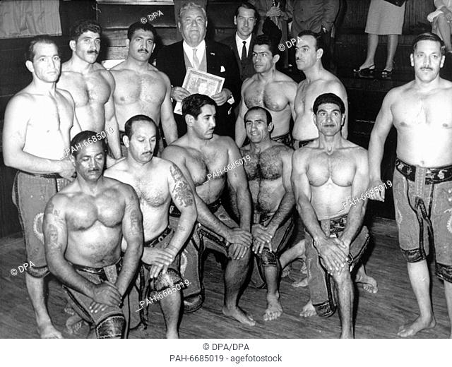 Politician and lawyer Carlo Schmid (m, back) visits a sports school in Teheran (Iran) in October 1964 and is surrounded by muscular men