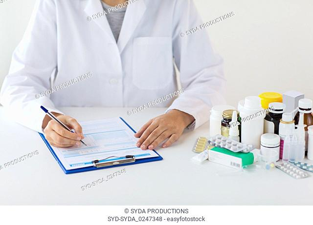 doctor with medicines and clipboard at hospital