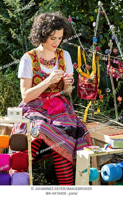 Button maker, young woman in colorful dirndl with Posamentenknopf Collier siting in garden and working on Posamentenknopf, with threads, material
