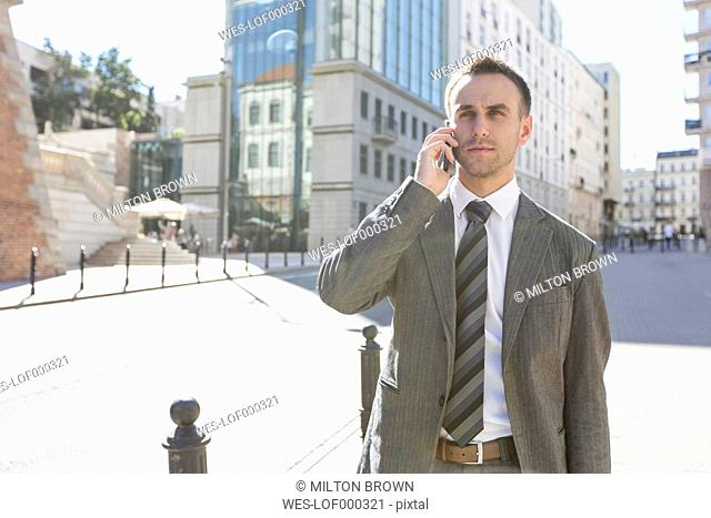 Poland, Warsaw, Businessman using mobile phone