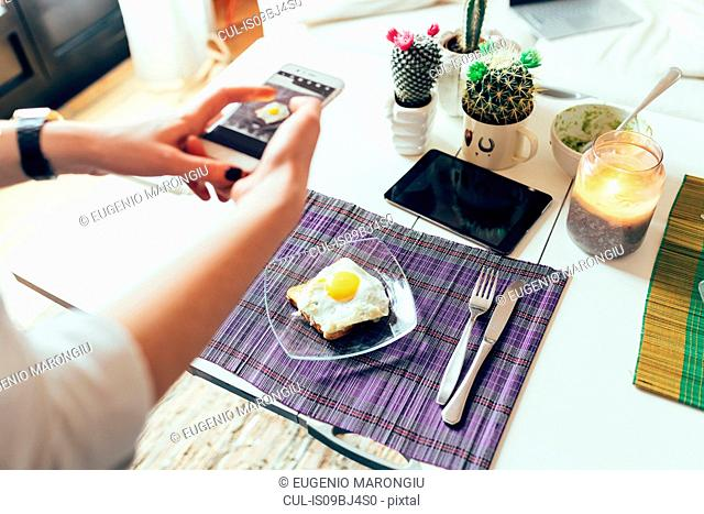 Woman photographing breakfast on mobile phone
