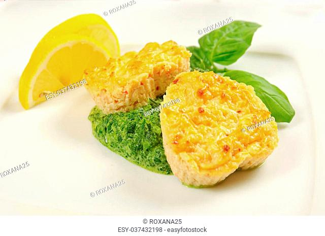 Fishcakes with lemon, basl leaves and green sauce in a restaurant