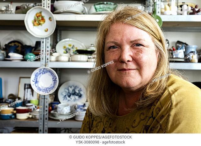 Tilburg, Netherlands. Portrait of a mature adult, female shop owner selling vintage household items