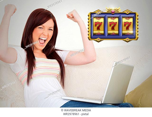 Casino slot machine 7's in front of woman celebrating playing on laptop computer