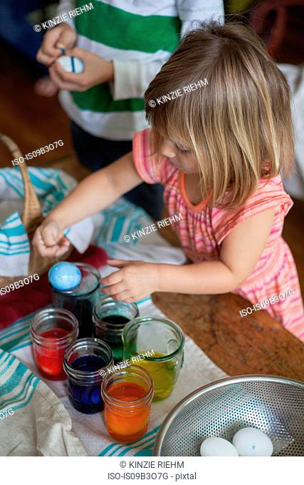 Girl and brother dyeing easter eggs in jars at table