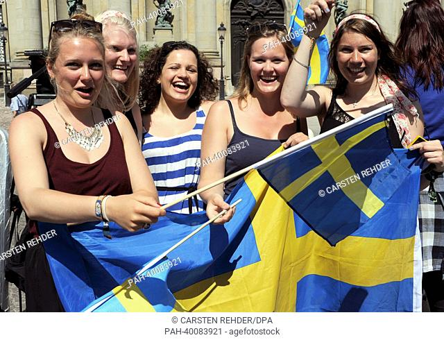 German tourists wave with Swedish flags waiting for the Royal Wedding of Swedish Princess Madeleine and her husband Chris O'Neill in Stockholm, Sweden