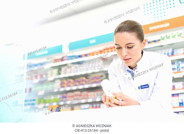 Pharmacist reading label on bottle in pharmacy