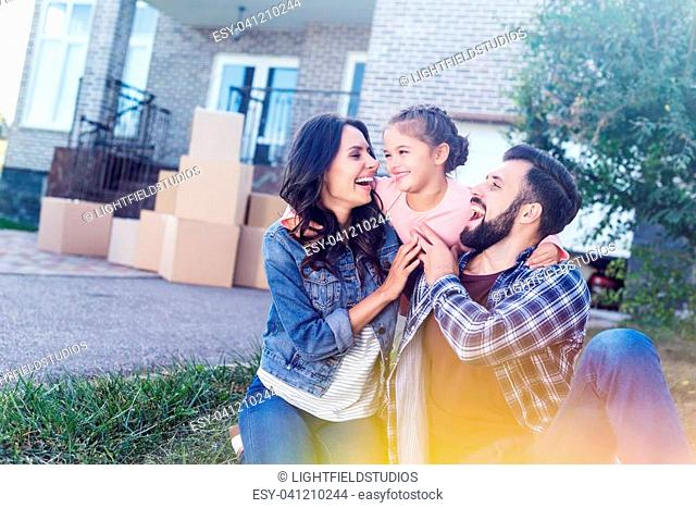 young family having fun together outdoors while sitting on grass