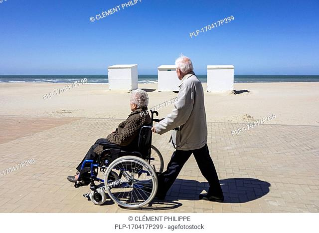 Retired husband taking disabled elderly wife in wheelchair for a walk on promenade along the coast on a cold sunny day in spring