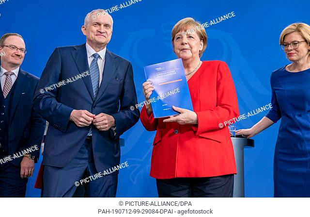 12 July 2019, Berlin: Federal Chancellor Angela Merkel (CDU) stands next to the Chairman of the Council of Experts Christoph M