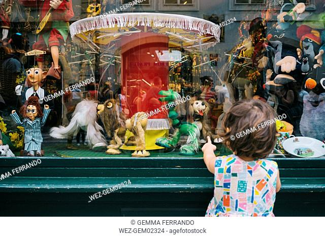 Czechia, Prague, back view of little girl standing in front of toy shop looking at puppets